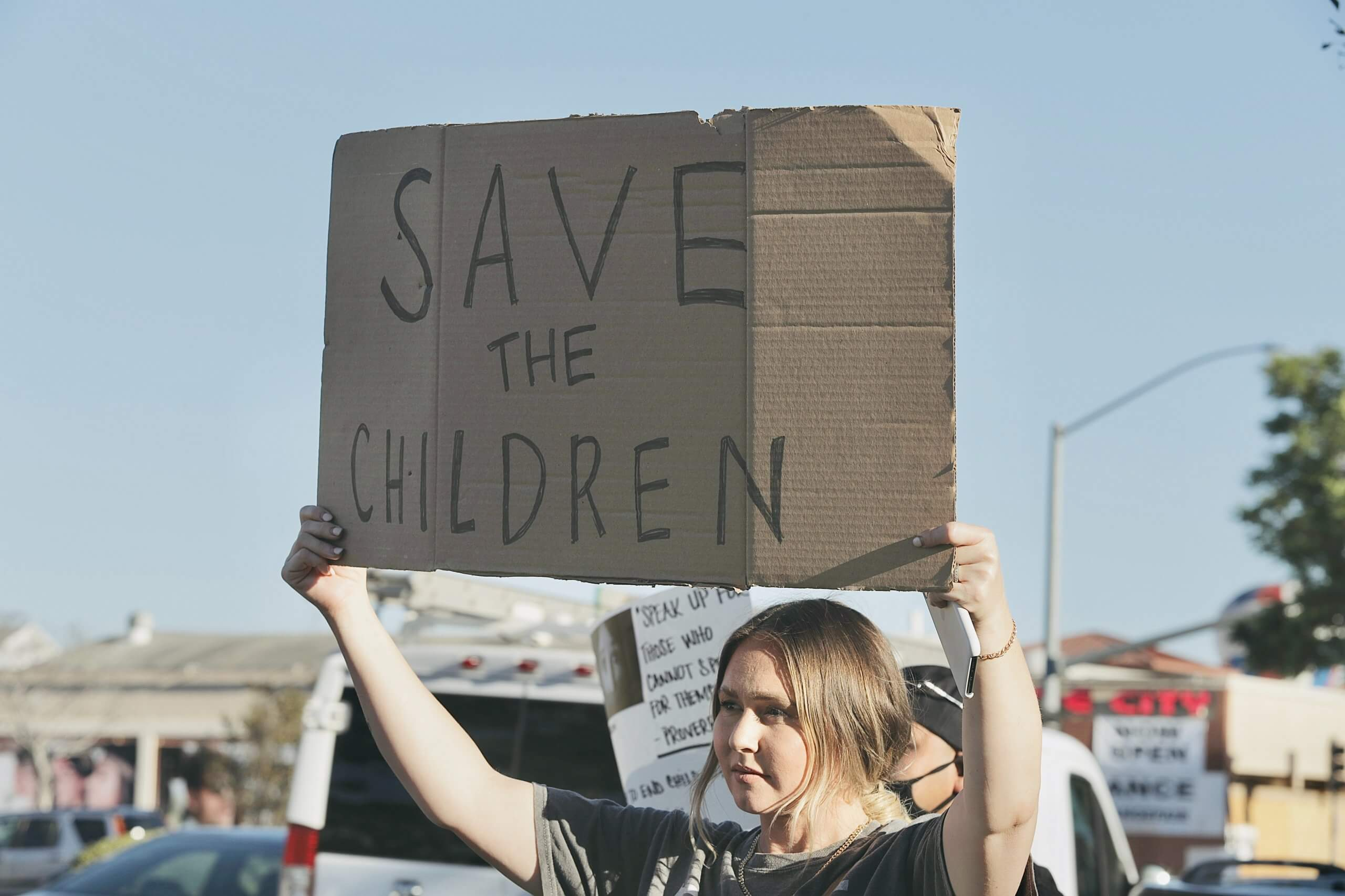Kvinna med plakat med texten: Save the children